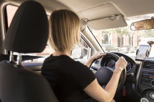Woman driving a car with phone using navigation