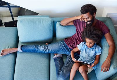 A father and daughter sitting on a couch using a tablet computer