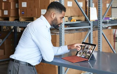 A man in a suit touching his Microsoft Surface Pro 7 while video conferencing with friends and colleagues.