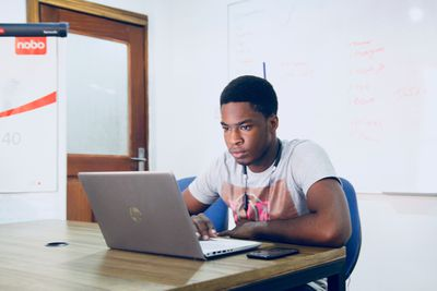 Young male in classroom working on a laptop