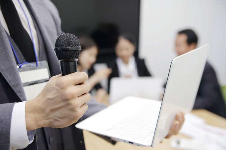 man holding microphone and laptop at business meeting