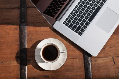 A close up of a MacBook laptop next to a cup of coffee on a brown desk