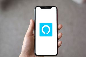 A person holding an iPhone with the Alexa app logo.