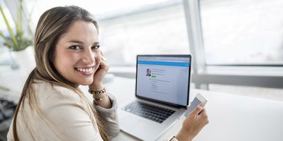 A woman using WebEx from her laptop in a brightly lit office
