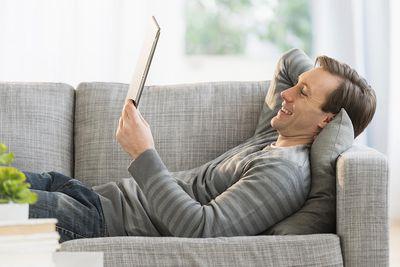 Man lying on sofa watching tablet pc