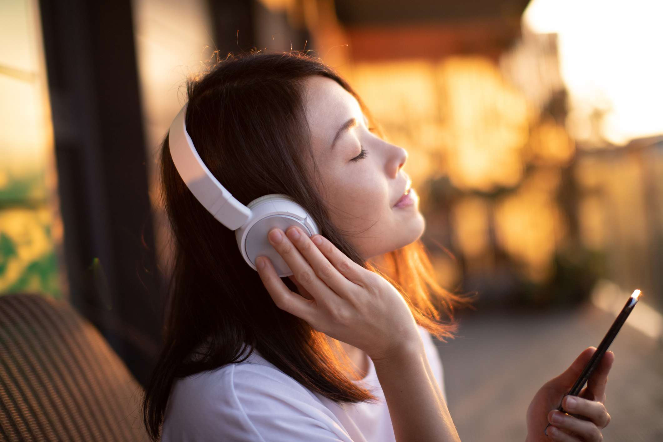 Close up of a young person listening through headphones, holding a smartphone.