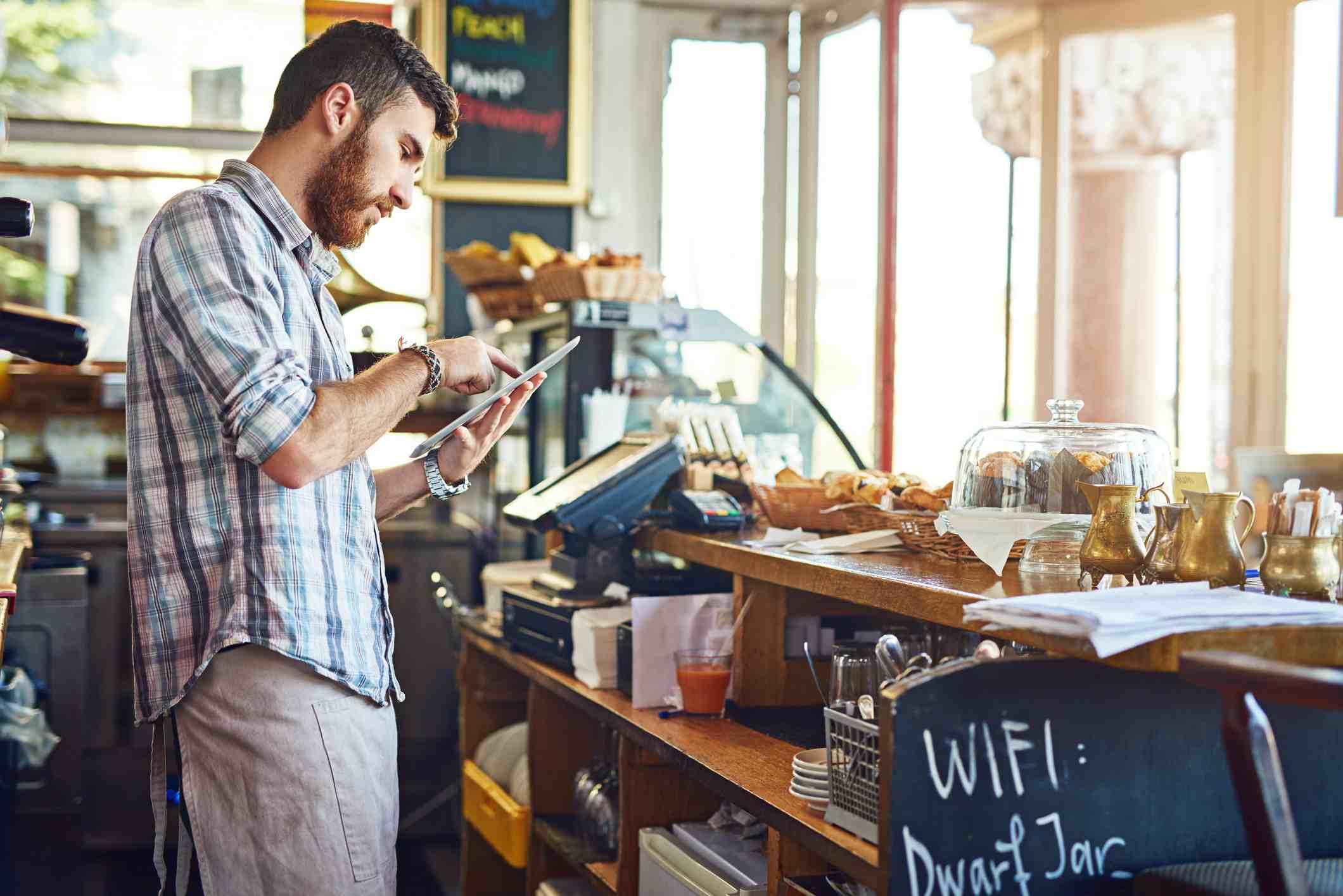 Man working in coffee shop using iPad