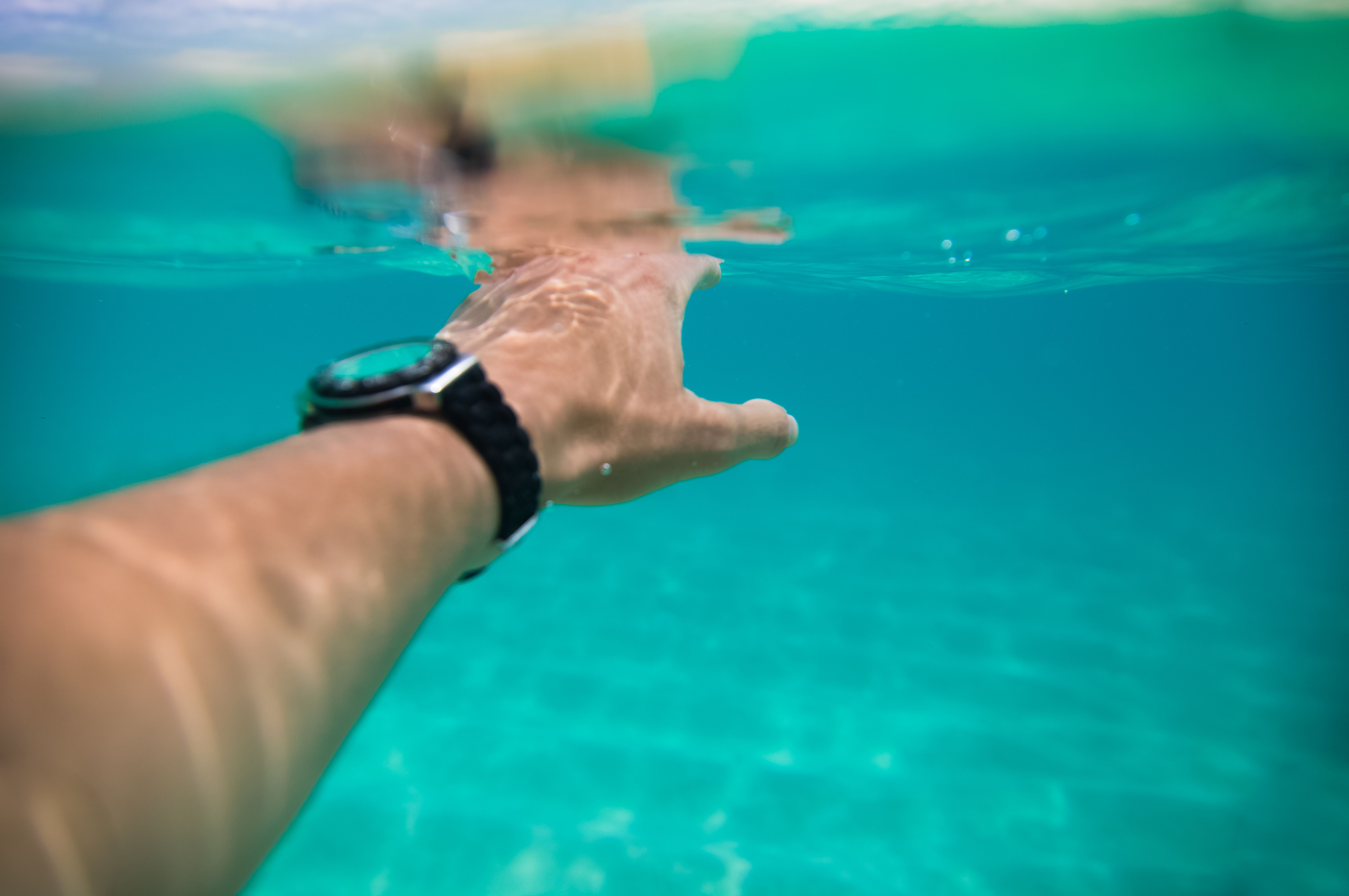 Man swimming under water with smartwatch.