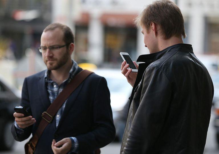 Two men looking at their phones walking on a sidewalk
