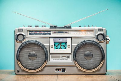 Retro outdated portable stereo boombox radio receiver with cassette recorder from circa late 70s front aquamarine wall background.