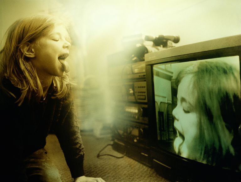 Young girl sticking tongue out at camera with image on tv