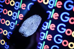A thumbprint is displayed on a mobile phone while the Google logo is displayed on a computer monitor