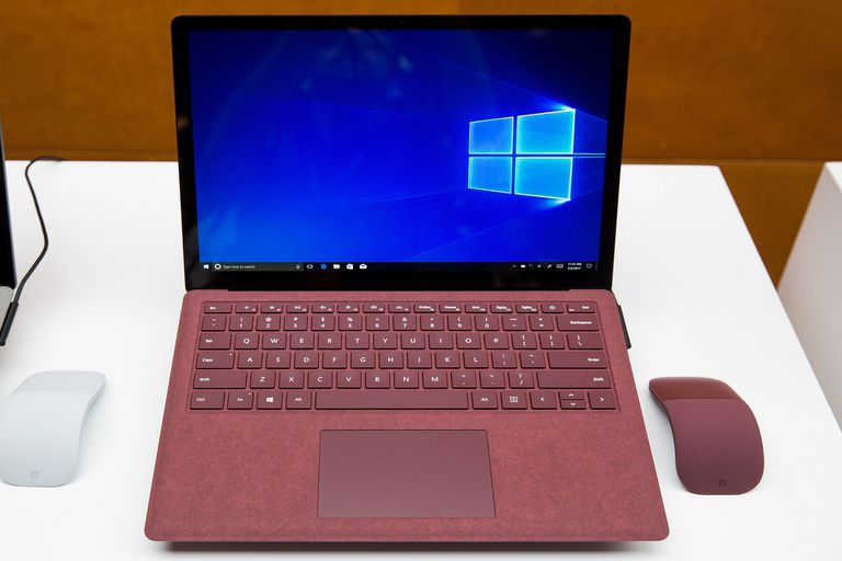 A screenshot of a red Microsoft Windows Surface laptop sitting on a white display. The laptop is sitting between two wireless mice: one white, one red.