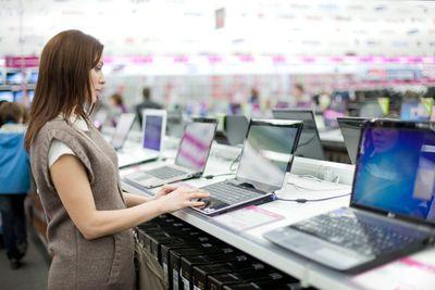 Woman browsing laptops at store