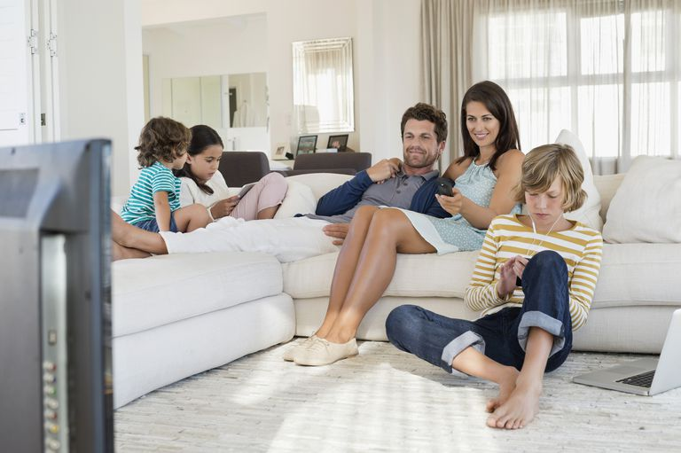 Family sitting on couch watching TV and using devices