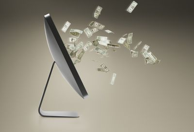 Personal computer and floating dollar bills coming out of screen