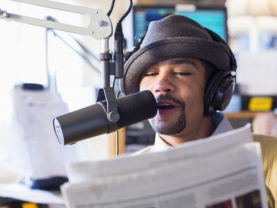 Disc jockey talking into mic in studio