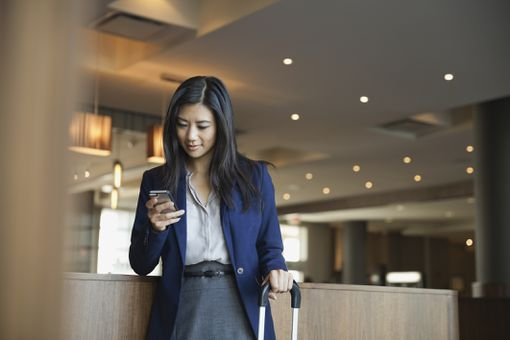 Businesswoman using smart phone in hotel lobby