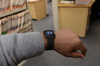 A man's arm wearing a Fitbit Versa with a designer clock face displayed.