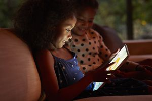 Two young girls playing on digital tablet, at night.