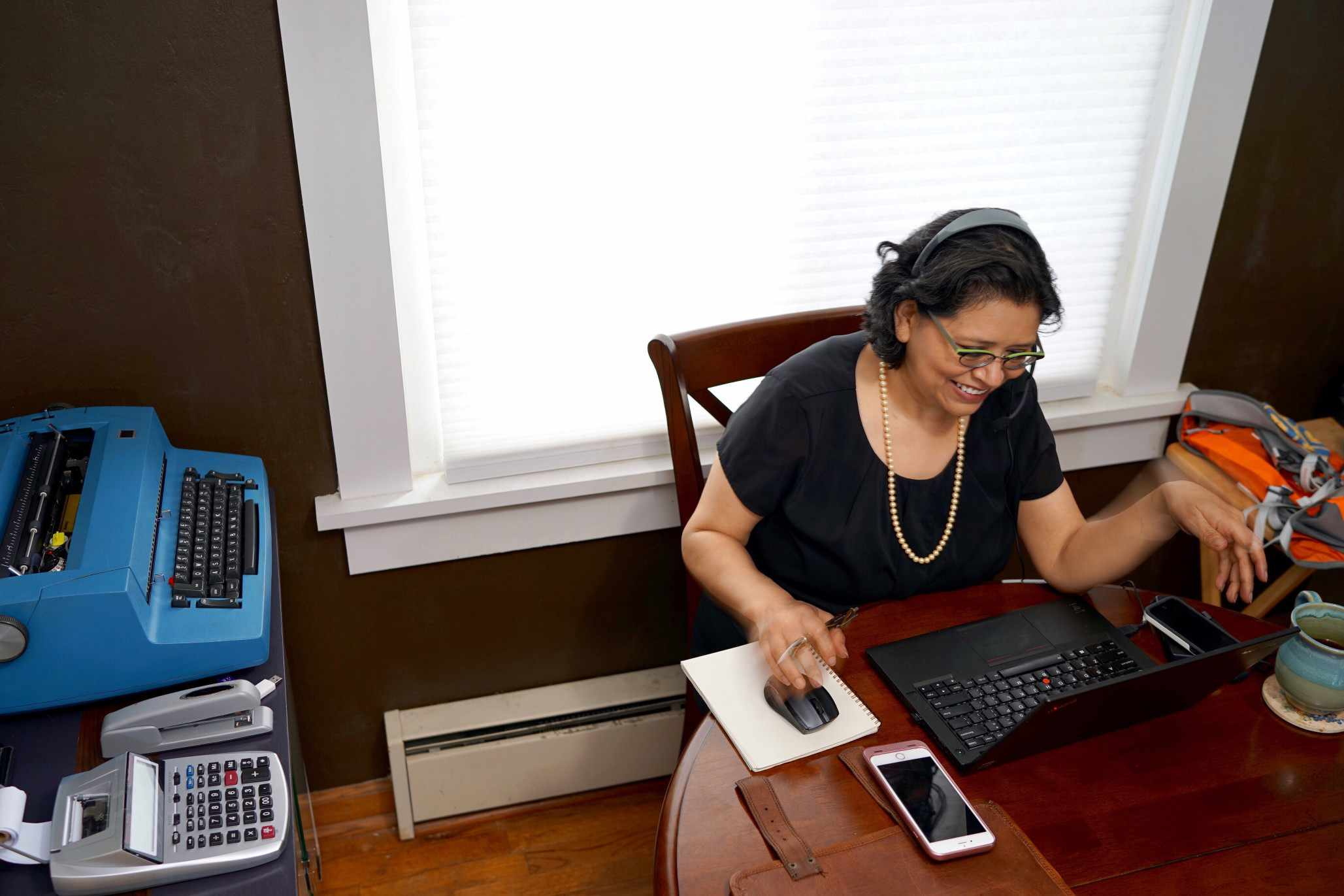 A woman participating on a video conference at the kitchen table.