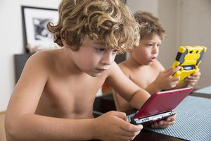 Boys playing with portable game console