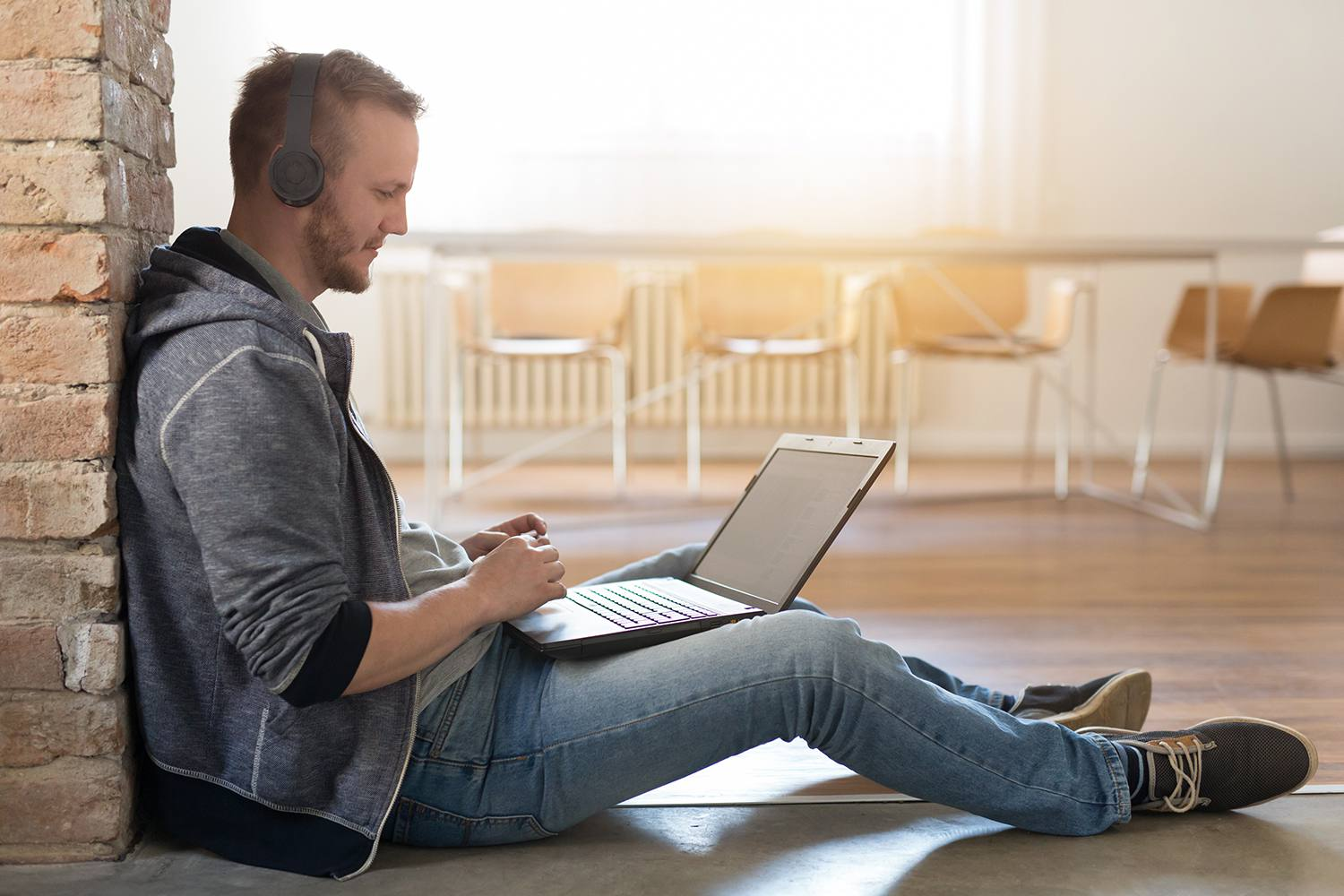 Remote worker with headphones and a laptop sitting