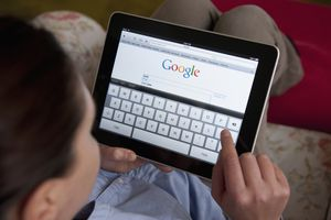 Woman searching on Google website using iPad tablet computer