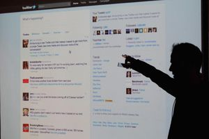 Twitter CEO Evan Williams is seen silhouetted against a screen