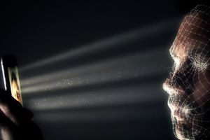 Man using face recognition on a mobile phone in a dark room
