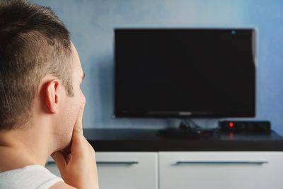 A man looks at a TV with a black, blank screen.