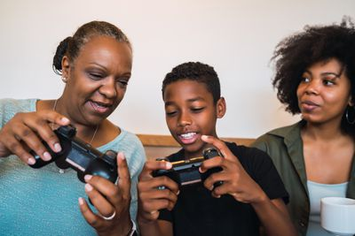 A family holding games controllers together