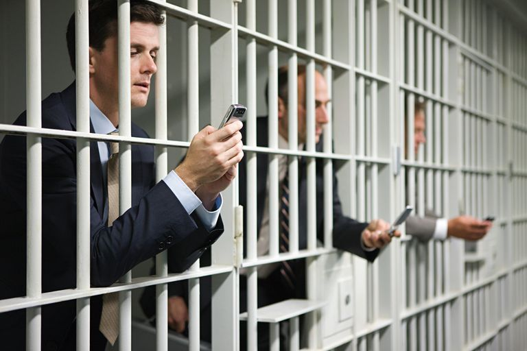 Businessmen in jail on their cell phones