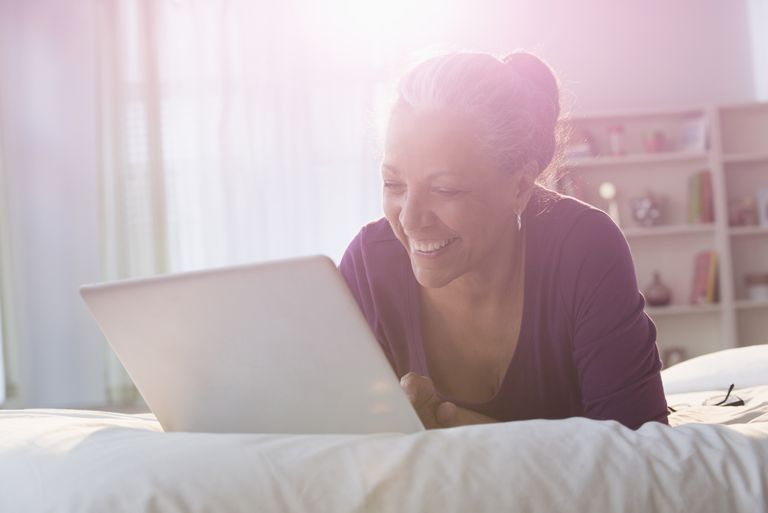 Older woman using laptop on a bed