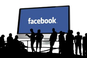 silhouettes of people standing in front of a large Facebook sign