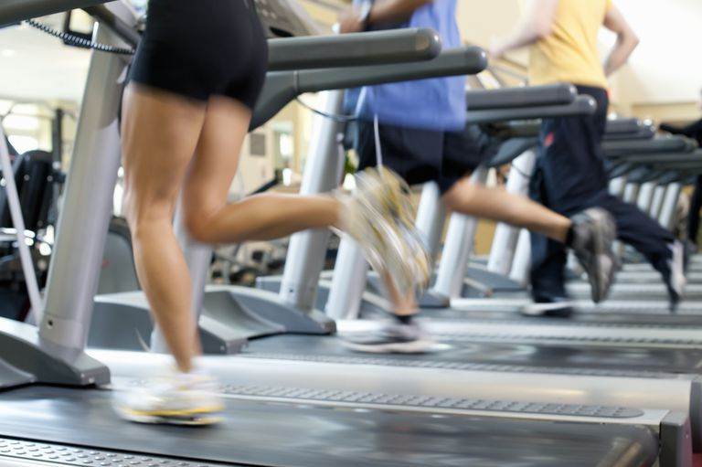 Blurred people running on treadmill