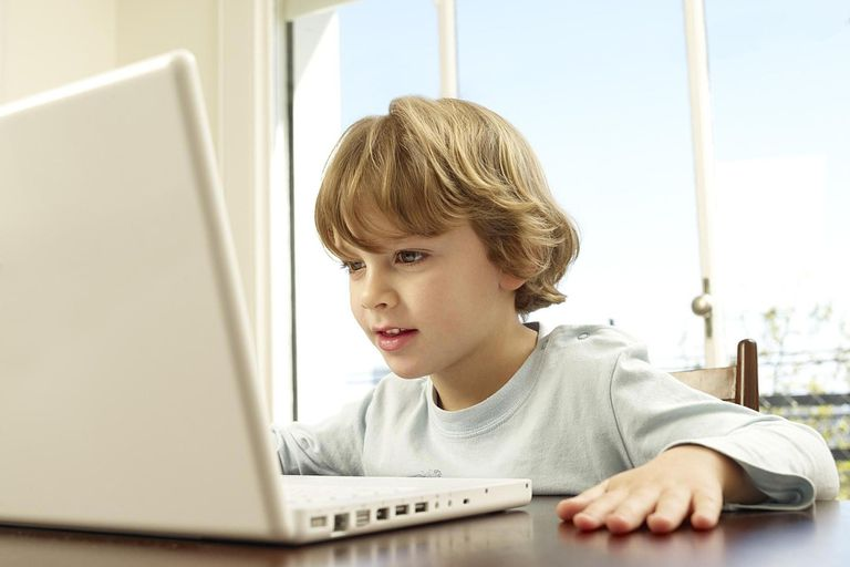 Boy (4-5) using laptop at home