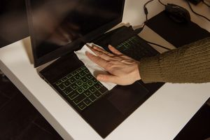 A person wiping a cloth across a laptop keyboard