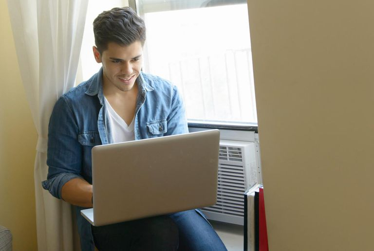 Young man sitting on window sill using laptop