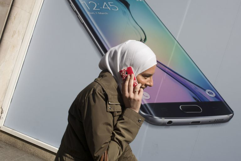 Woman with a headscarf talking on an Android phone in front of a picture of an Android phone.