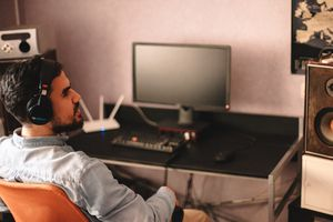 A man sitting at a desk with headphones in. A computer and router sit in the background.