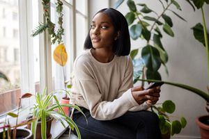 A woman sitting surrounded by plants holding her smartphone
