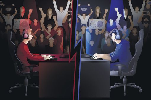 Two gamers sitting at the table opposite each other with a crowd of cheering fans on the background.