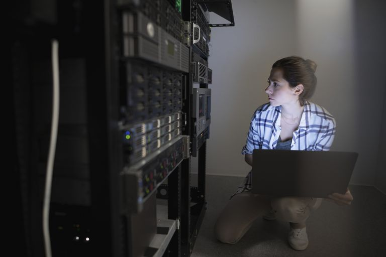 A young network administrator looks at a server rack.
