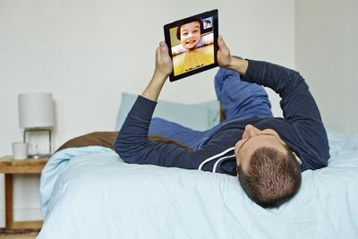 Man using iPad to video chat with young boy