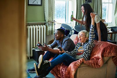 A group of friends sitting on and near a sofa cheering at a game unfolding