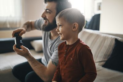 Happy little boy playing computer game with his father at home