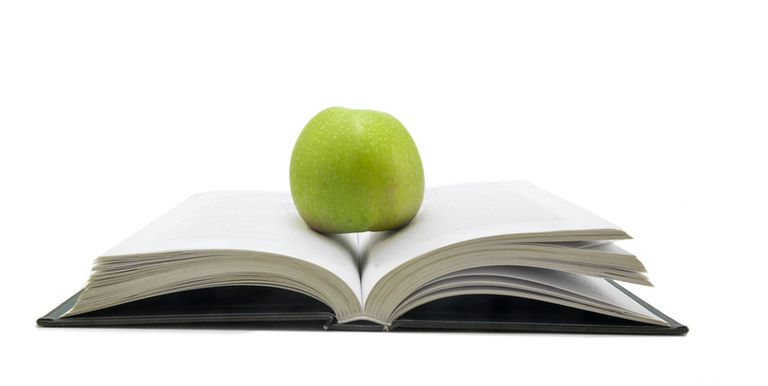 Apple sitting on pages of a book