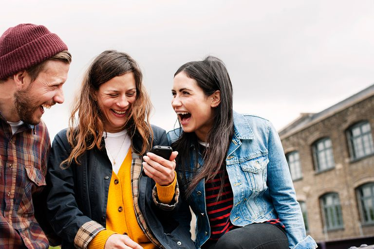 Three people looking at a phone and laughing