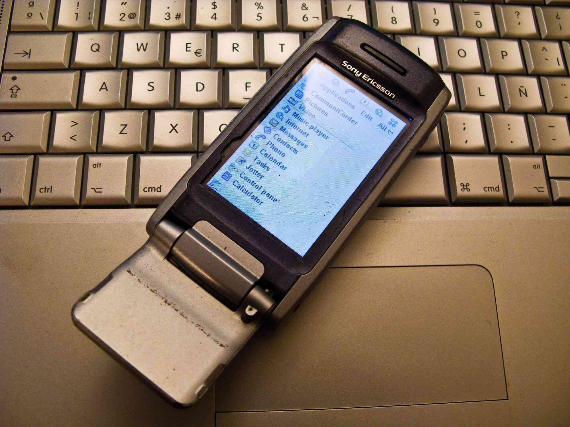 Photo of an old Sony Ericsson cell phone resting on a laptop
